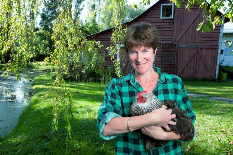 Mulher que guarda uma galinha fora do celeiro fotos de stock royalty free