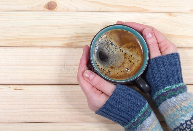 Mulher que guarda uma xícara de café no fundo de madeira fotografia de stock