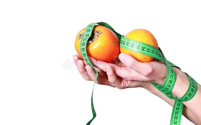 Mulher que guardam frutos exóticos saudáveis e uma fita métrica pronta para fazer dieta fotografia de stock