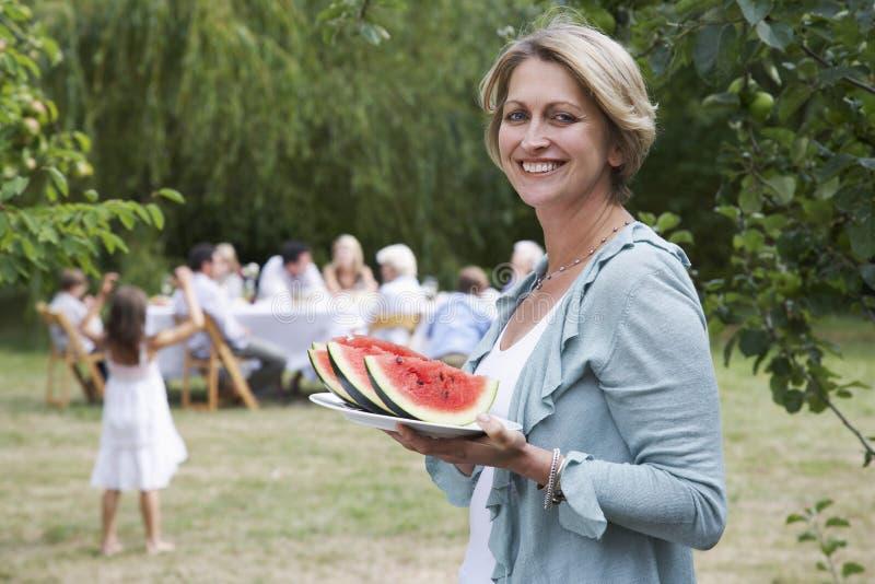 Mulher que guardara fatias de melancia com a família no fundo imagem de stock