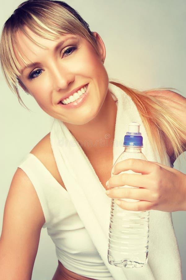 Mulher que guardara a garrafa de água imagem de stock