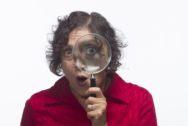 Mulher que guardara a lupa até seu olho, horizontal fotos de stock royalty free