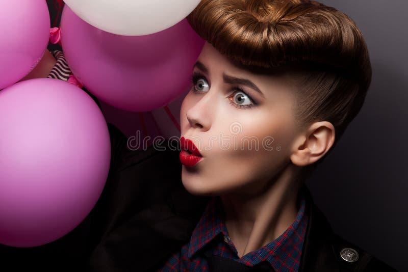 Mulher que guardara o grupo de balões de ar coloridos imagem de stock