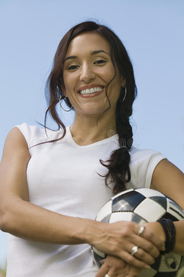 Mulher que guardara o retrato do baixo ângulo de bola de futebol. imagem de stock royalty free