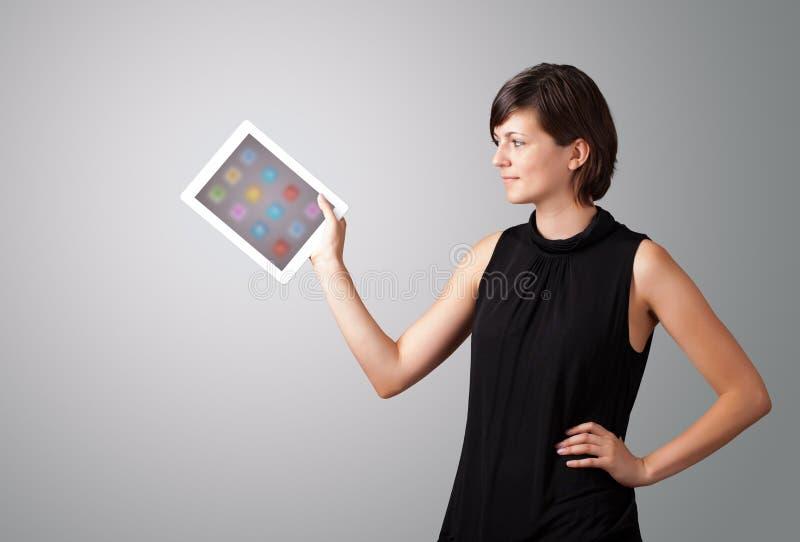 Mulher que guardara a tabuleta moderna com ícones coloridos fotos de stock
