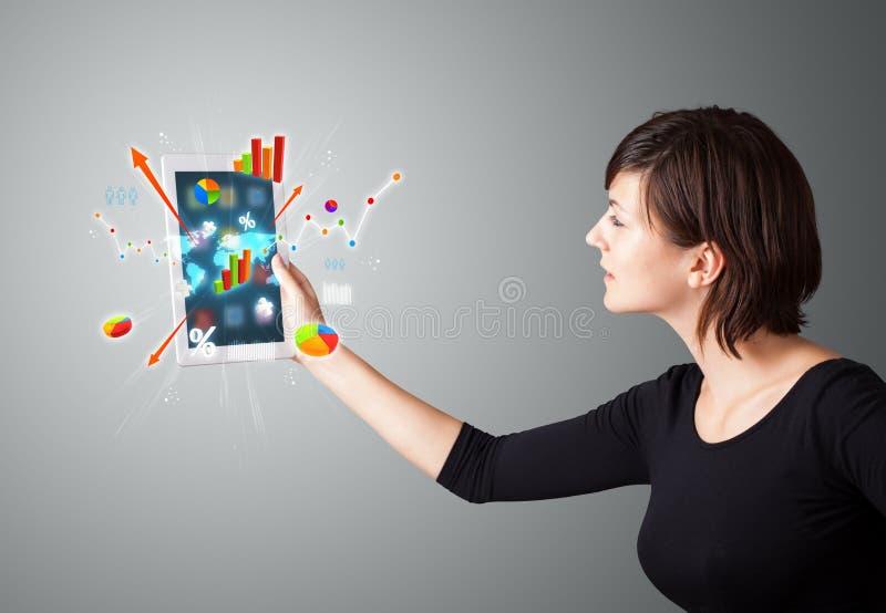 Mulher que guardara a tabuleta moderna com diagramas e gráficos coloridos imagem de stock royalty free