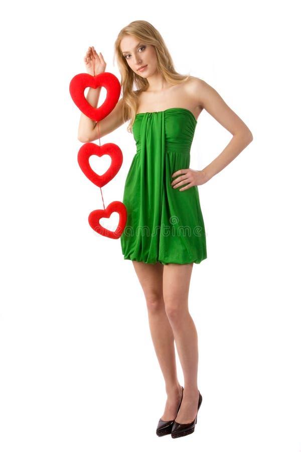 Mulher que guardara três corações fotos de stock royalty free