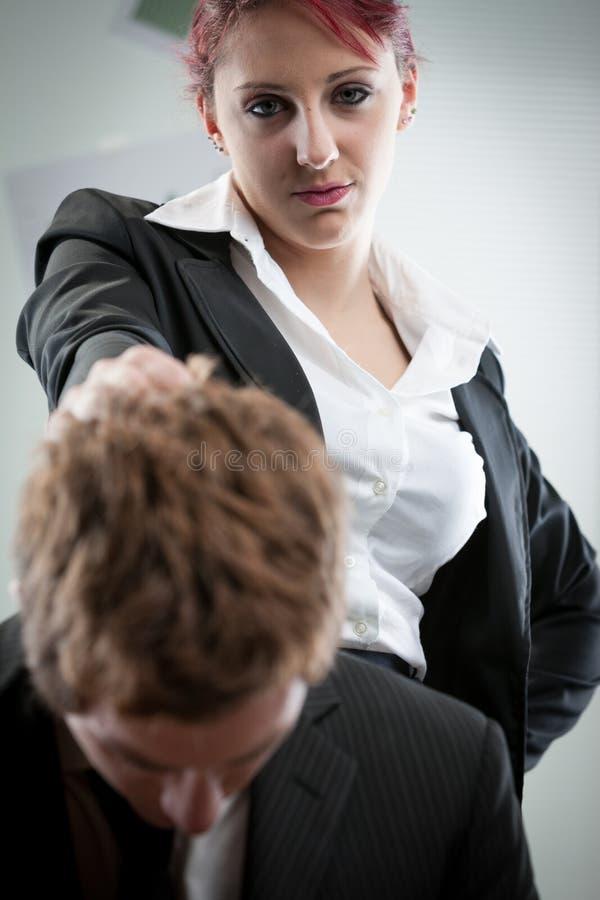 Mulher que humilha um homem no local de trabalho imagens de stock