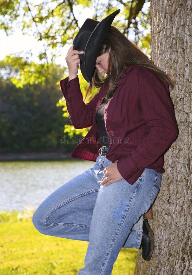 Mulher que inclina-se de encontro à árvore foto de stock royalty free