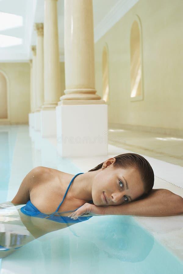 Mulher que inclina-se na borda da piscina fotos de stock