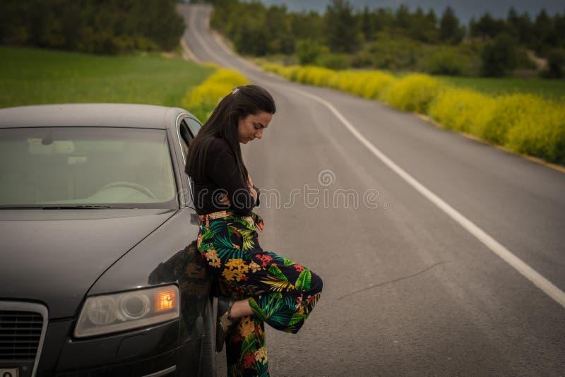 Mulher que inclina-se no carro foto de stock
