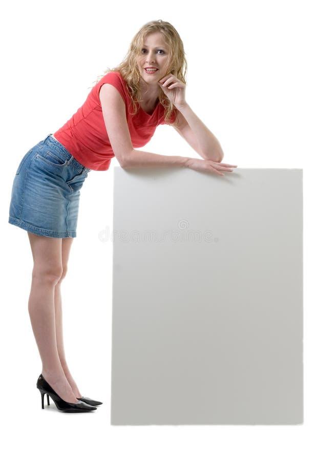 Mulher que inclina-se no sinal em branco fotos de stock