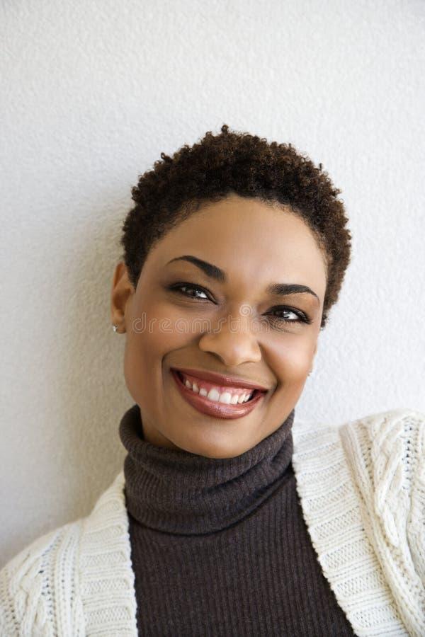 Mulher que inclina-se no sorriso branco da parede. fotografia de stock