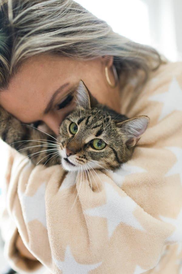 Mulher que joga com gato - abra?ando e beijando fotos de stock royalty free
