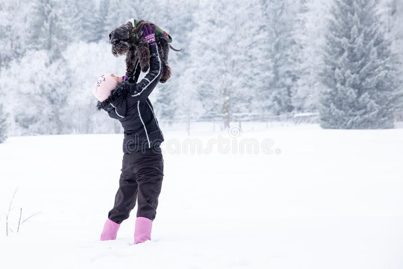 Mulher que joga com seu c?o na neve no inverno tomando imagens pelo selfie do telefone fotos de stock royalty free