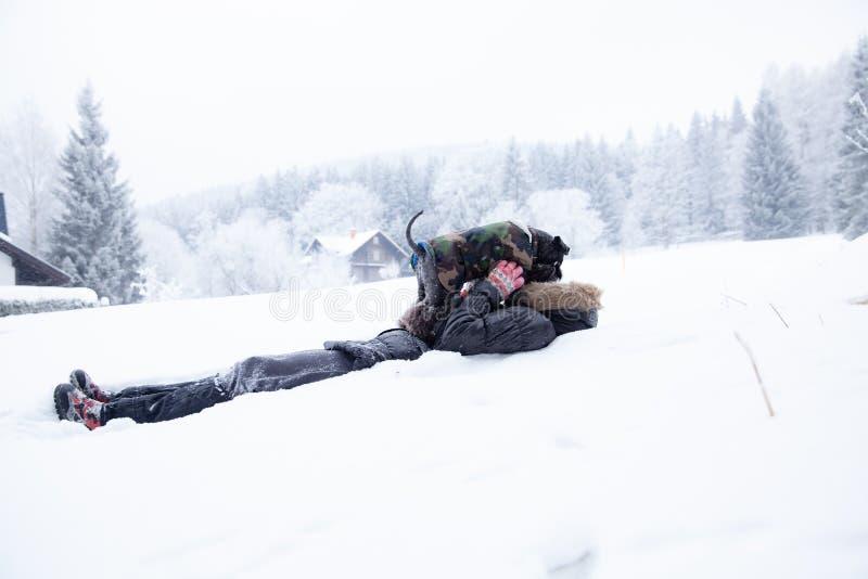 Mulher que joga com seu c?o na neve no inverno tomando imagens pelo selfie do telefone imagem de stock