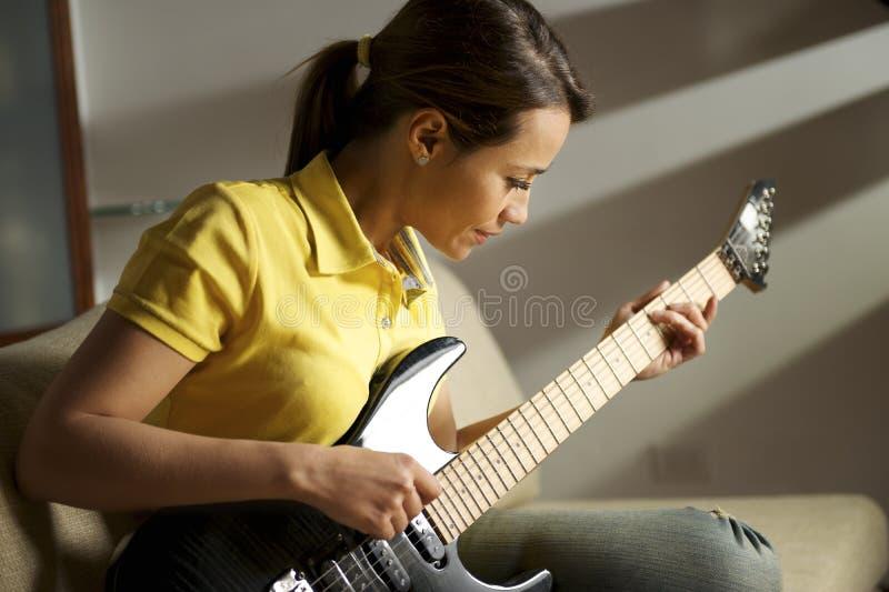 Mulher que joga e que treina com guitarra elétrica em casa imagem de stock