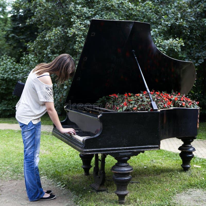 Mulher que joga em um piano velho fotos de stock