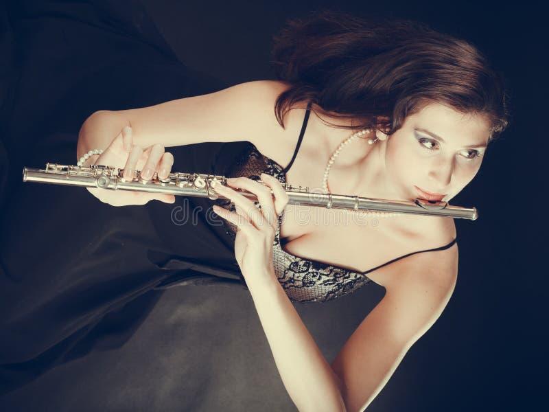Mulher que joga a flauta transversal no preto imagem de stock royalty free