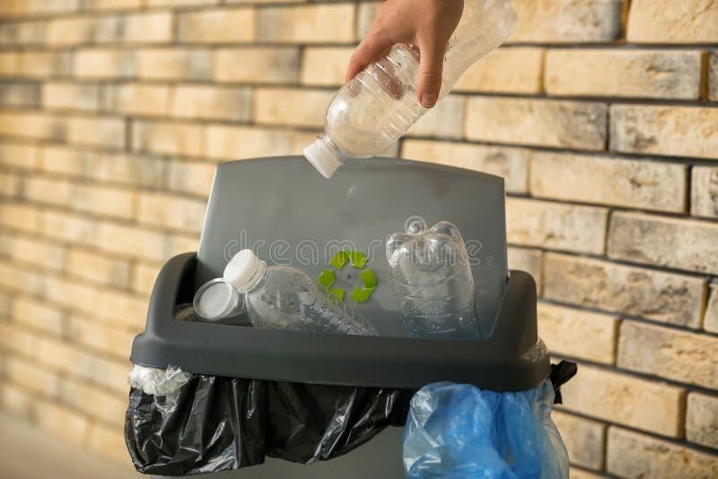 Mulher que joga a garrafa plástica no escaninho de lixo perto da parede de tijolo fotografia de stock royalty free