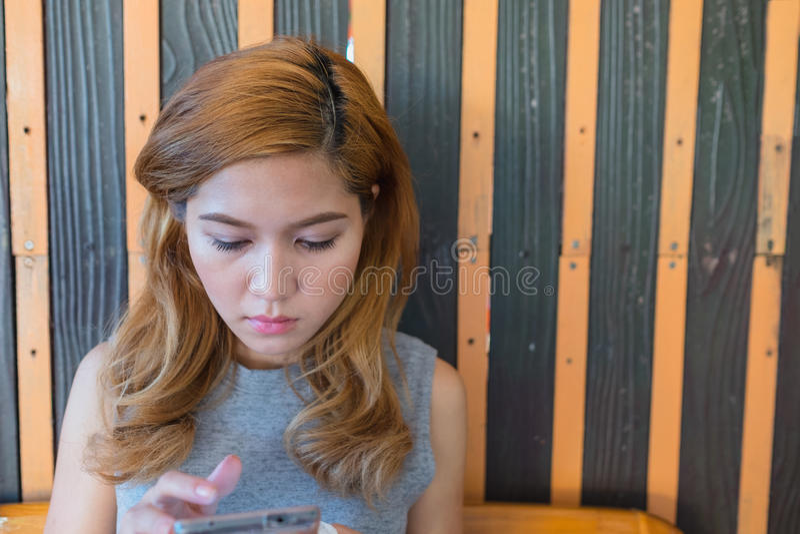 A mulher que joga a mão móvel senta-se fotos de stock royalty free