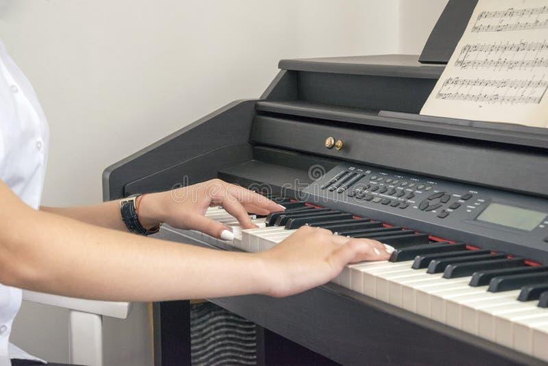 Mulher que joga no piano elétrico foto de stock royalty free
