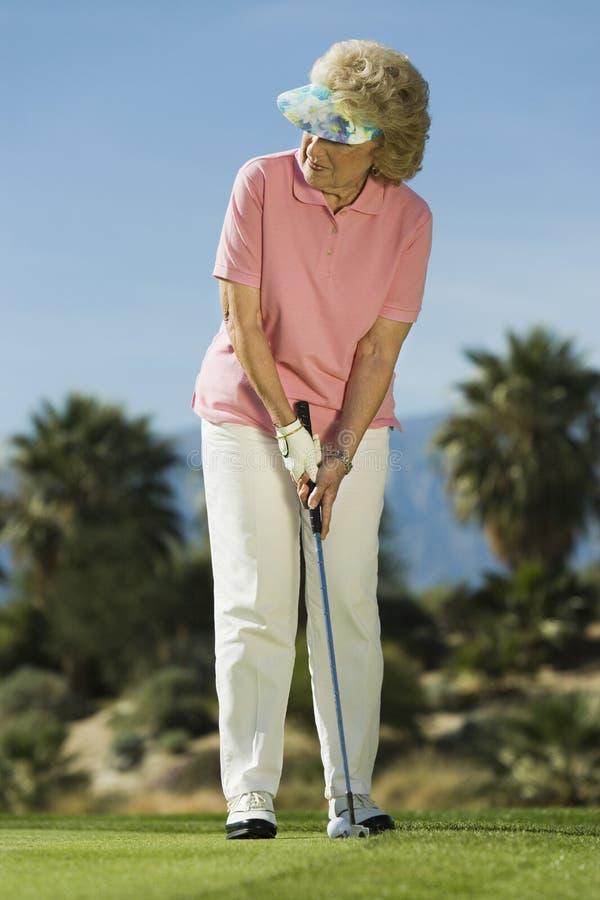 Mulher que joga o golfe imagem de stock royalty free