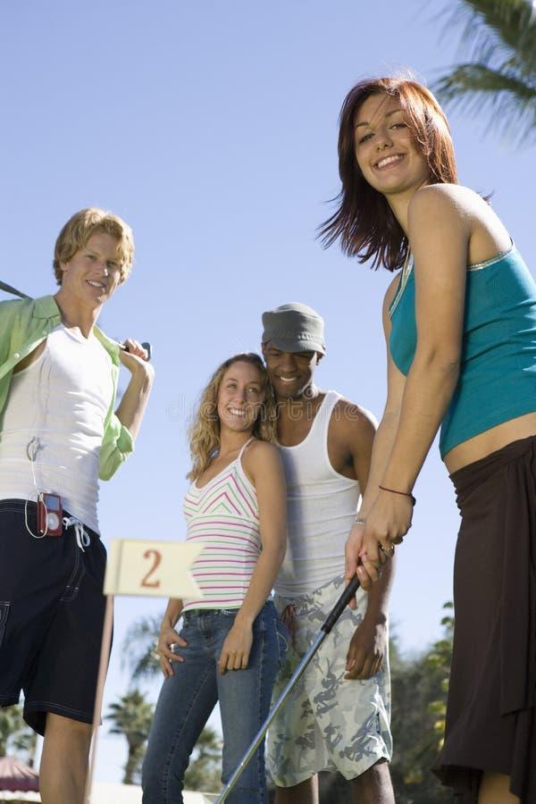 Mulher que joga o golfe com amigos fotos de stock royalty free