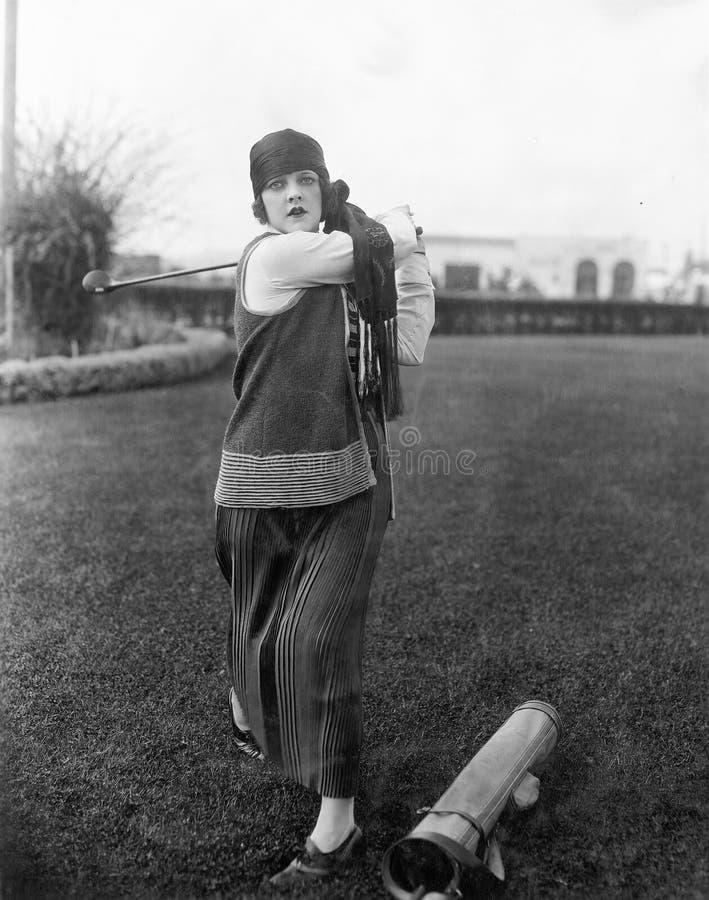 Mulher que joga o golfe (todas as pessoas descritas não são umas vivas mais longo e nenhuma propriedade existe Garantias do forne imagens de stock royalty free