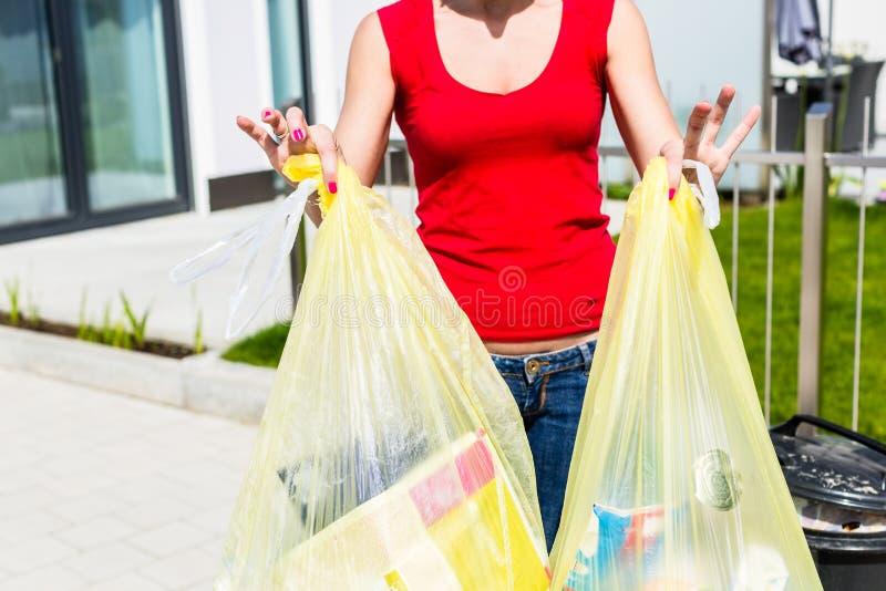 Mulher que joga o lixo afastado no recipiente fotos de stock royalty free