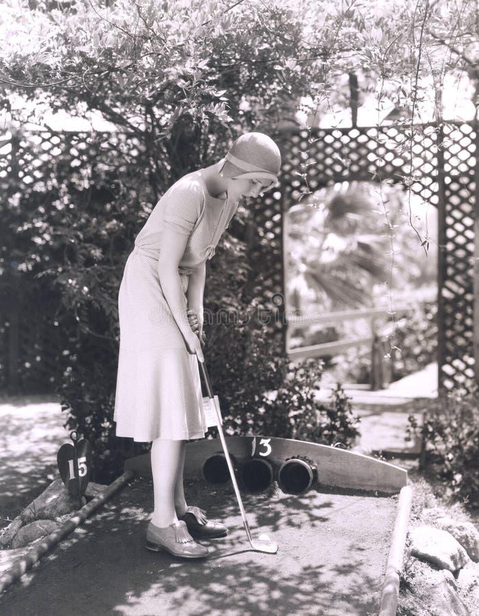 Mulher que joga o mini golfe fotografia de stock