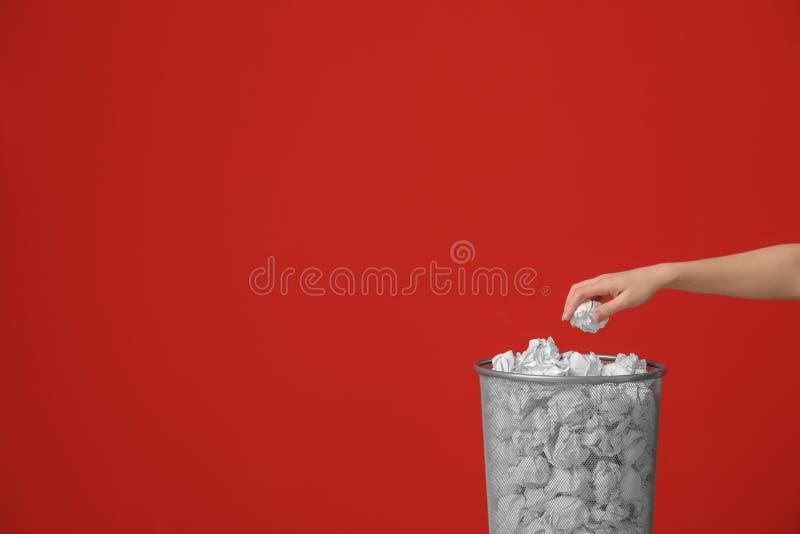 Mulher que joga o papel amarrotado no escaninho do metal contra o fundo da cor imagem de stock royalty free