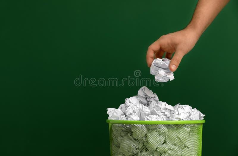 Mulher que joga o papel amarrotado no escaninho do metal no fundo da cor, close up fotos de stock royalty free