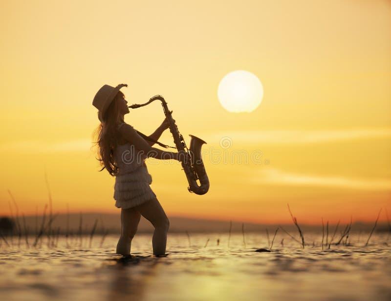 Mulher que joga o saxofone na água com sunst fotografia de stock royalty free