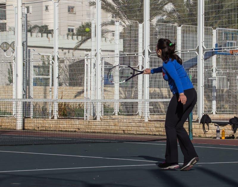 Mulher que joga o tênis na corte e nas batidas a raquete na bola fotografia de stock royalty free