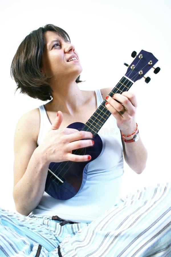 Mulher que joga o ukulele imagem de stock