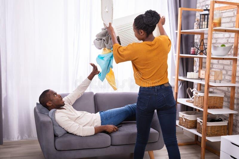 Mulher que joga a roupa suja no marido pregui?oso imagens de stock