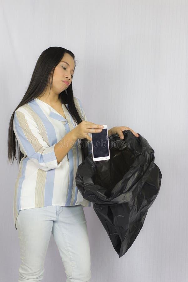 Mulher que joga seu telefone no saco de lixo, levantamento isolado no fundo cinzento fotografia de stock