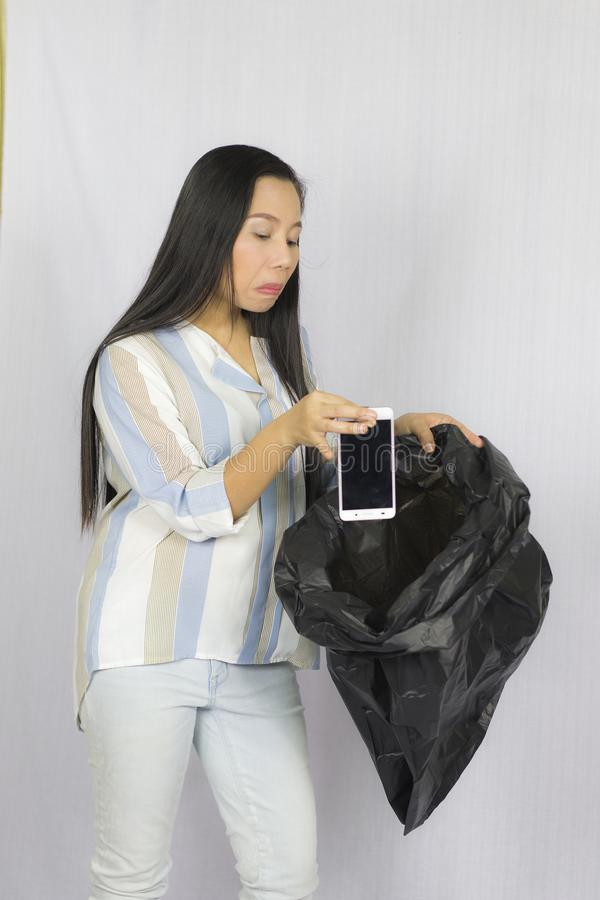Mulher que joga seu telefone no saco de lixo, levantamento isolado no fundo cinzento fotos de stock royalty free