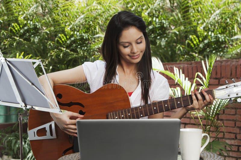 Mulher que joga uma guitarra imagens de stock royalty free