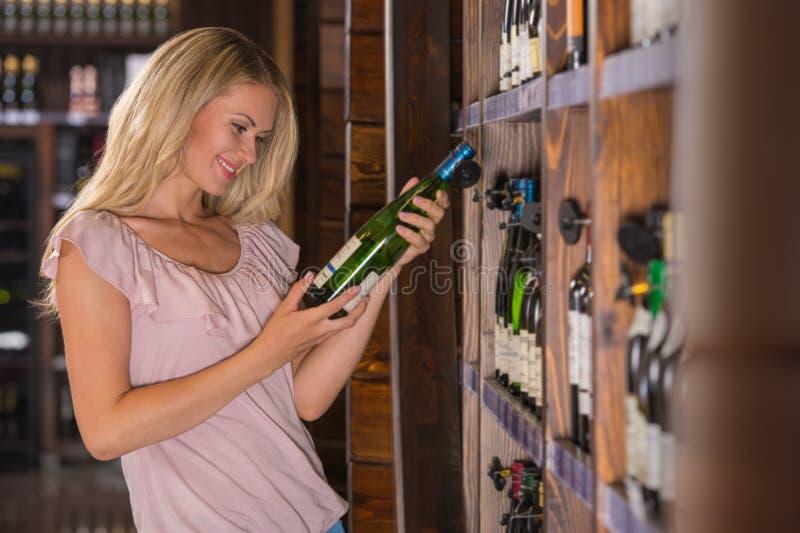 Mulher que lê a etiqueta atrás de uma garrafa do vinho imagem de stock royalty free