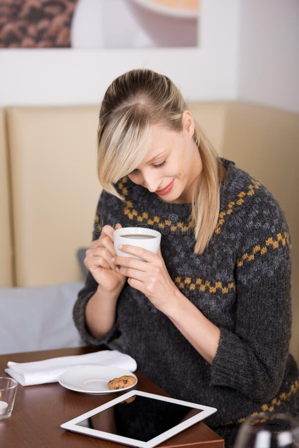 Mulher que lê um eBook em um café fotos de stock