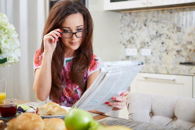 Mulher que lê um jornal imagens de stock