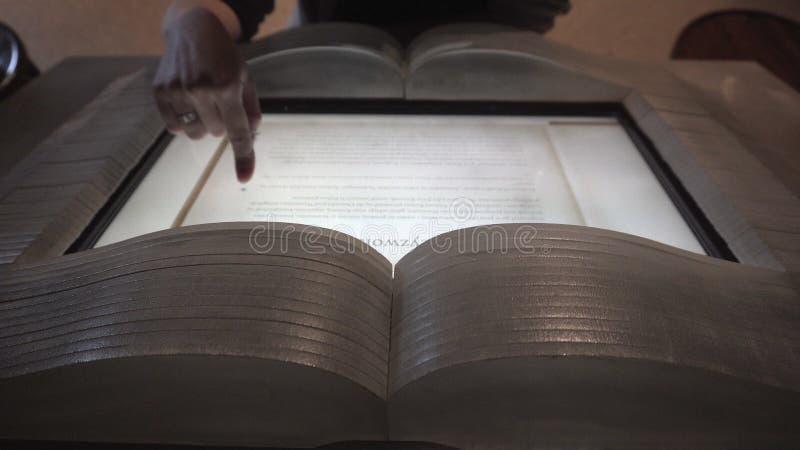 Mulher que lê um livro em um Ebook no museu imagens de stock royalty free