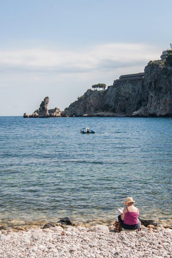Mulher que lê um livro na praia perto de Giardini - Naxos, Sicília, Itália imagens de stock