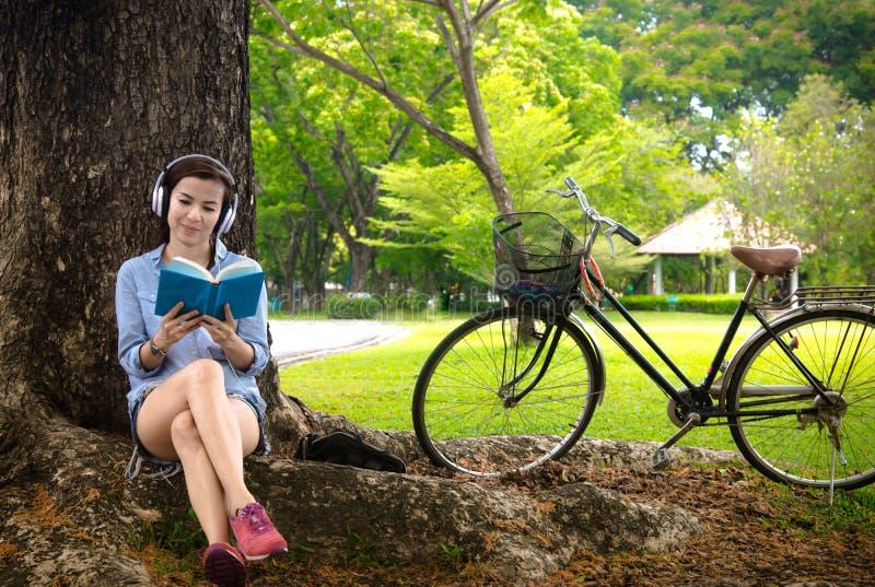 Mulher que lê um livro quando música de escuta fotografia de stock royalty free