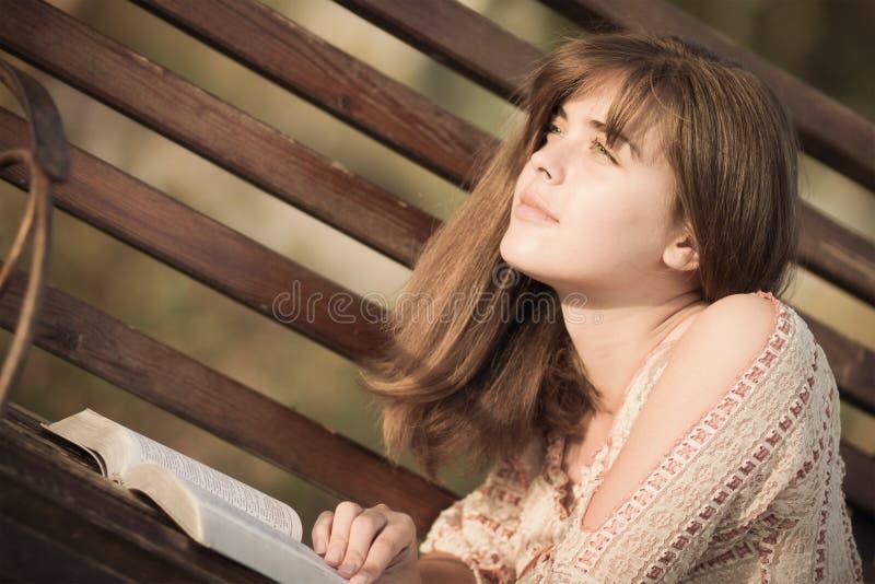 Mulher que lê um livro que encontra-se no banco imagens de stock