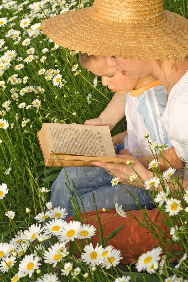Mulher que lê uma história a seu rapaz pequeno foto de stock