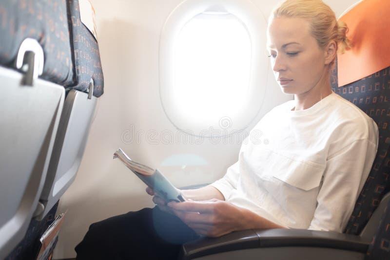 Mulher que l? em voo o compartimento no avi?o Leitura f?mea do viajante assentada na cabine do passanger Calha de brilho de Sun fotos de stock