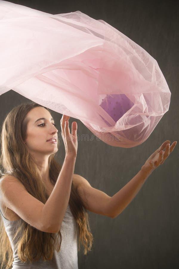 Mulher que lanç a tela cor-de-rosa com uma bola para dentro fotografia de stock royalty free